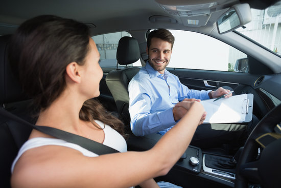 Young woman on a driving lesson from a young man